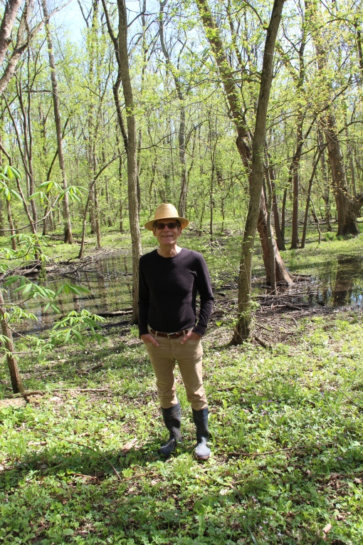 Michael stands in wetlands area home to skunk cabbage and salamanders.